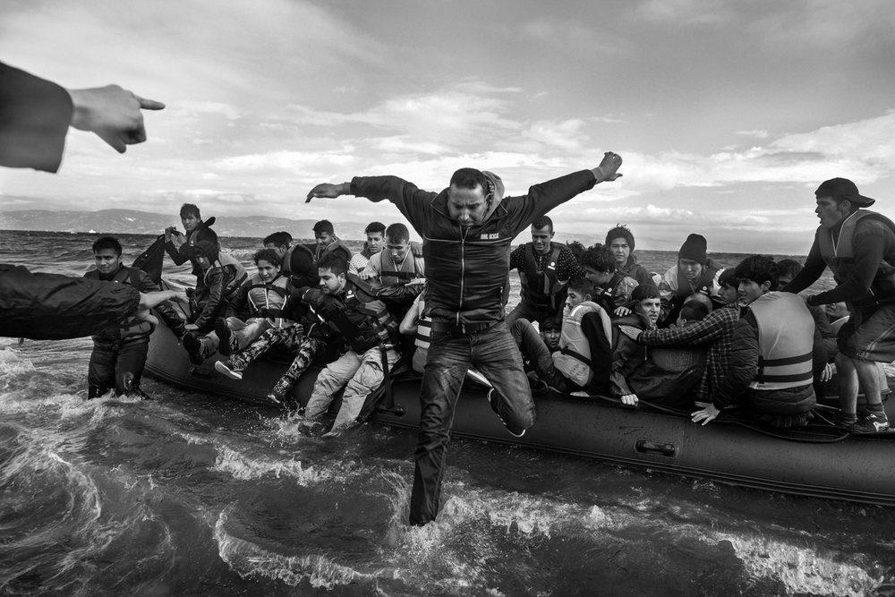 Refugees primarily from Syria, Iraq and Afghanistan are helped by volunteers as they disembark boats near Scala, on the island of Lesvos, Greece on September 30, 2015. The Agean sea is particularly rough, with the first signs of winter storms beginning today. Many refugees were sea sick, some to the point of life threatening conditions due to dehydration and cold.