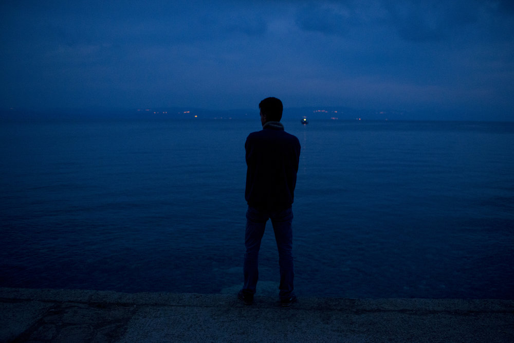 A refugees looks towards Turkey after arriving on the Greek island of Lesbos.