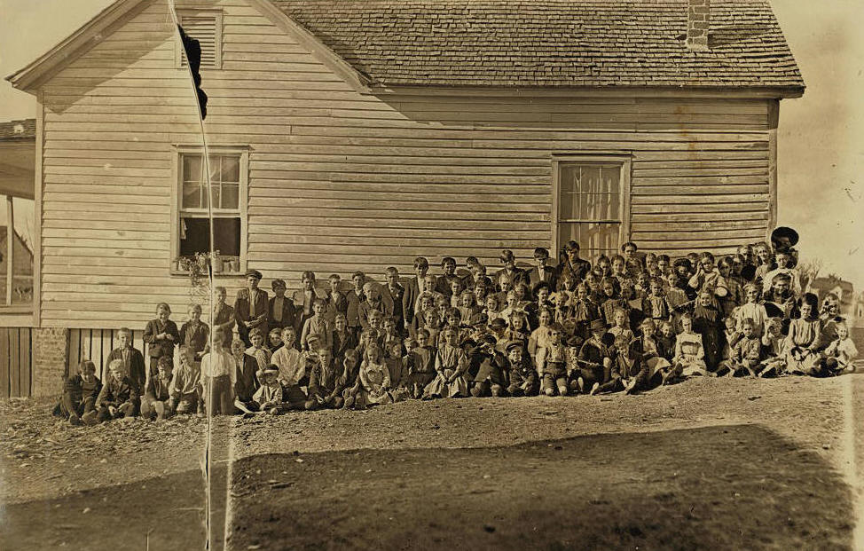 Lewis Hine caption:  This is where the mill children go to school. Lancaster, S.C. Enrollment 163– attendance, usually about 100. There are over 1,000 operatives in the mill. These are all that go to school from this mill settlement, which is geographically a part of Lancaster, but on account of the taxes has been kept just out of the corporate limits. Nov. 30/08. Location: Lancaster, South Carolina.