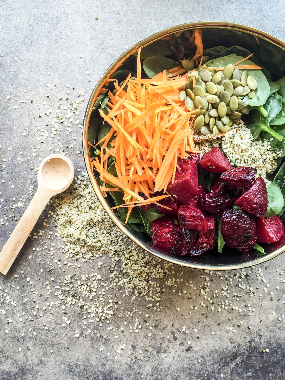 Roasted beet salad with spinach, hemp seeds, pepitas, and carrots.