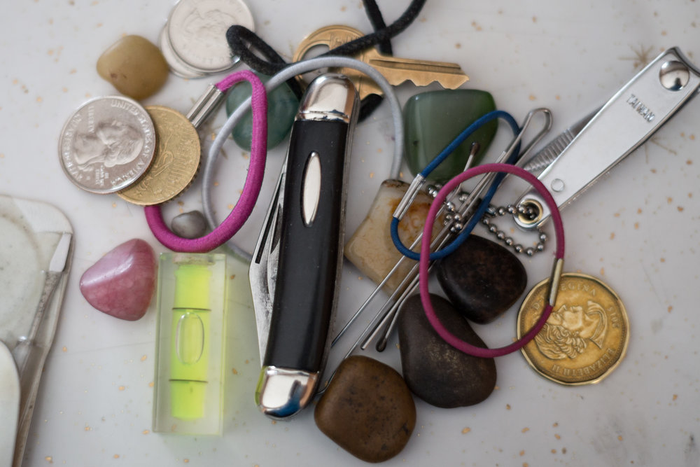 My dad's pocket contents. When I was younger, I had long hair as did my sisters. We were constantly losing our hair ties and my dad had them on hand for us. We used to give him little rocks which he still has.