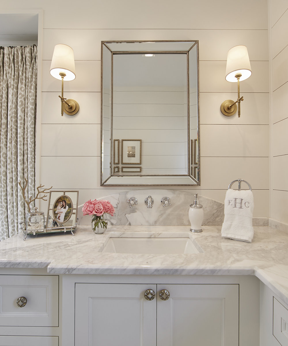 The master bathroom has a glamorous feel with its marble countertops, gold accents and original porcelain hexagon floor tiles. The white shiplap walls tie the room in with the styling of the rest of the house.