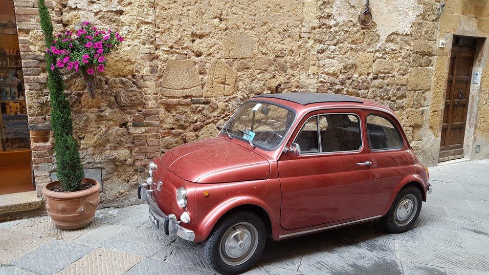 A vintage Fiat 500 parked in Pienza