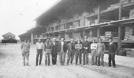 Vintage style photography of ten men standing in a row in from from a lumberyard