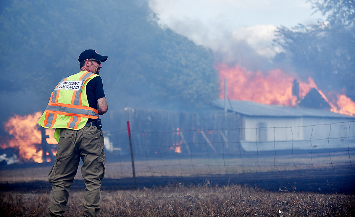 Evergreen Fire and Rescue Chief Williams looks out over the structure fire/grassland fire that filled the skies over Evergreen with smoke on Tuesday, August 4. (Brenda Ahearn/Daily Inter Lake)