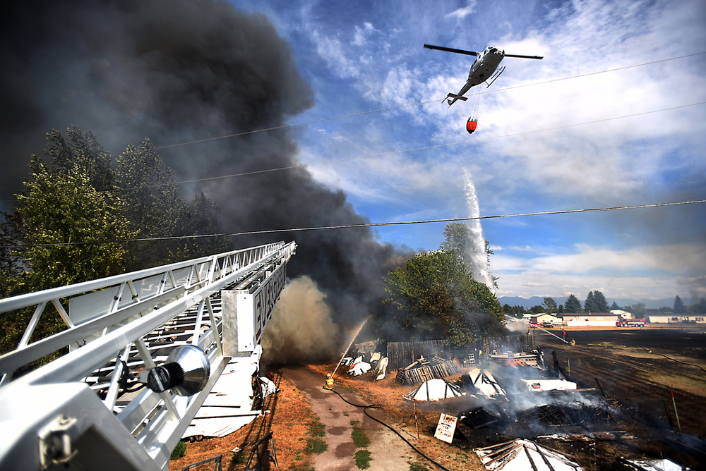View from atop the Evergreen Fire and Rescue ladder truck of a fire on Mountain View Drive in Evergreen on Wednesday, August 5. The helicopter is from the Department of Natural Resources and Conservation. (Brenda Ahearn/Daily Inter Lake) (Brenda Ahearn/Daily Inter Lake)