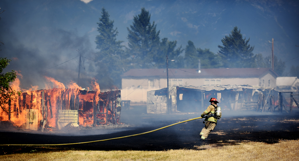 A firefighter battles a fire in an outbuilding south of the main structure fire on Wednesday, August 5, on Mountain View Drive in Evergreen. (Brenda Ahearn/Daily Inter Lake)