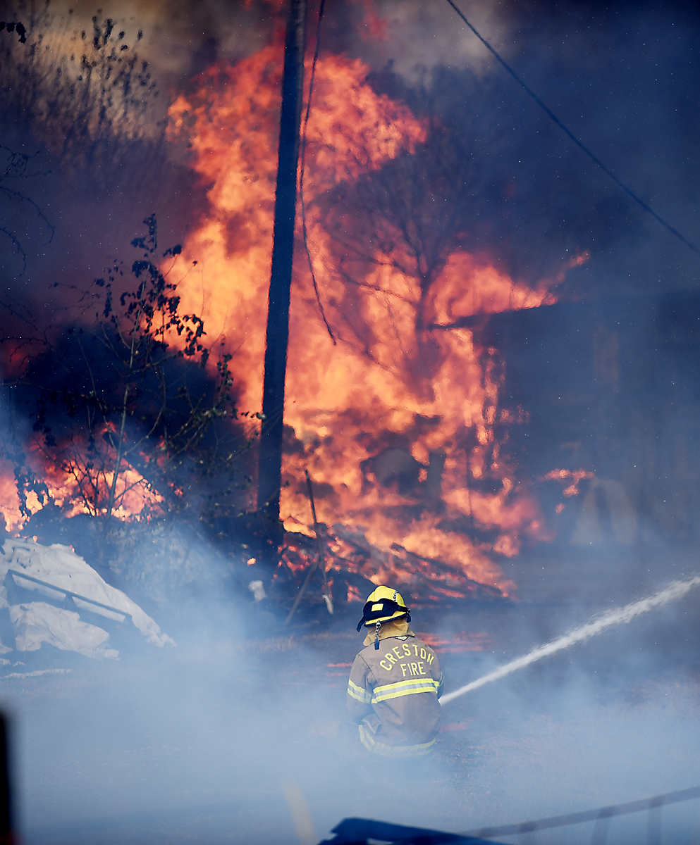 A Creston firefighter battles the blaze at a structure fire/grassland fire on Mountain View Drive in Evergreen on Wednesday, August 5. (Brenda Ahearn/Daily Inter Lake)