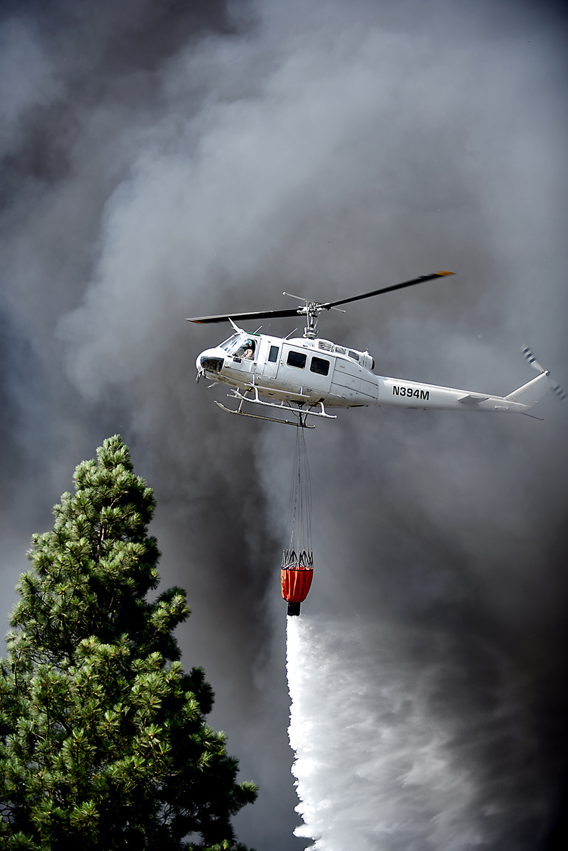A DNRC helicopter flies through smoke to drop water on the scene of a massive fire on Mountain View Drive in Evergreen on Wednesday, August 5. Evergreen Fire and Rescue were joined by the Kalispell and Creston fire departments, the Flathead County Sheriff's Office, forest firefighters and other first responders.  (Brenda Ahearn/Daily Inter Lake)