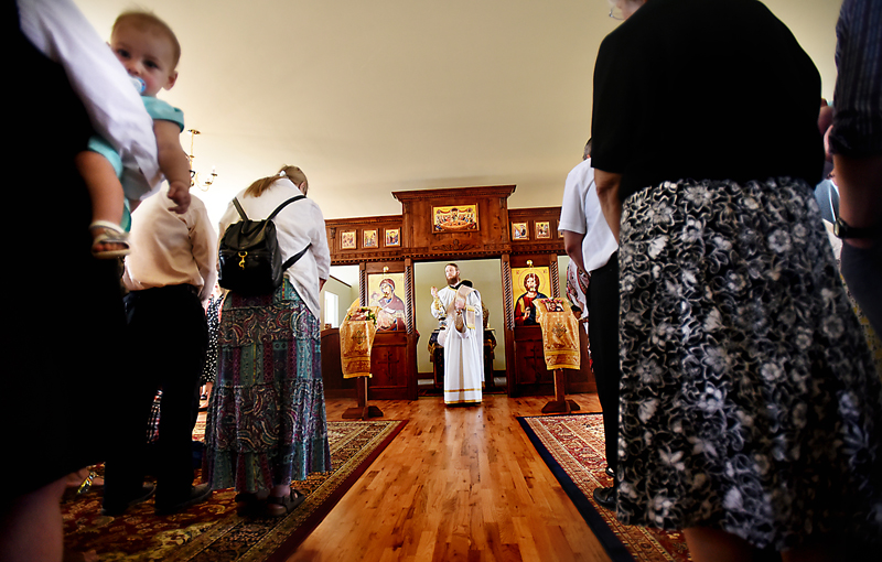 "The Rev. Daniel Kirk looks out over the parish during the blessing of the temple on Sunday, July 19, at Saint Herman Orthodox Church. Kirk was ordained later that day. ""I was also filled with such joy at the sight of each one of these faces that I have come to know and love,"" recalls Kirk. ""It felt like a little piece of Heaven."" (Brenda Ahearn/Daily Inter Lake)"