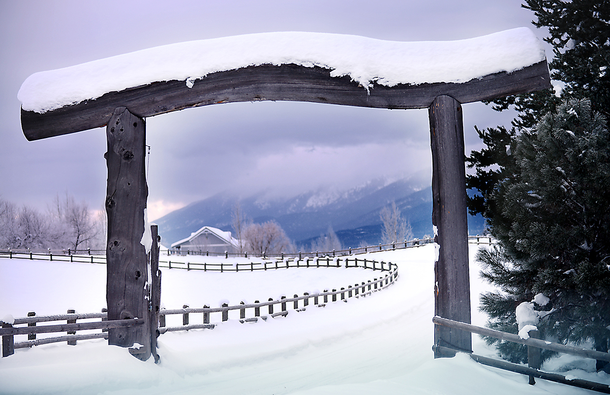 A large snow covered gate makes a frame for a winter scenic near Echo Lake on Thursday morning, January 8. (Brenda Ahearn/Daily Inter Lake)