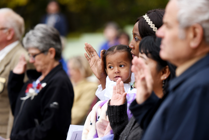 Sandrine Tochem of Chad gives the Naturalization Oath as she hold her two-year-old daughter Alexa at the Naturalization Ceremony in Glacier National Park on Wednesday, September 21. (Brenda Ahearn/Daily Inter Lake)
