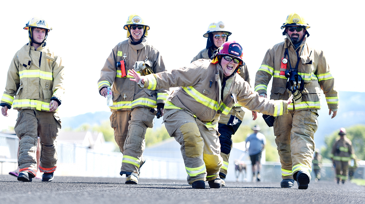 "This photo makes me happy. Smith Valley firefighter Danielle Teske smiles as she and other firefighters do laps in their gear to raise funds for the Smith Valley Fire Department on Sunday, July 31, at Legends Stadium in Kalispell as part of a fundraiser after an arsonist destroyed the Foy's Lake Station. According to Smith Valley Fire Chief DC Hass the community has been very generous in the aftermath of the fire. ""The public support has been very humbling, "" said Haas. ""And the neighboring departments have been amazing."" I laid down on the track hoping for a cool angle in the bight afternoon light. And Teske decided to mess with me. But I got the shot and she laughed out loud when I told her this one would make the paper."