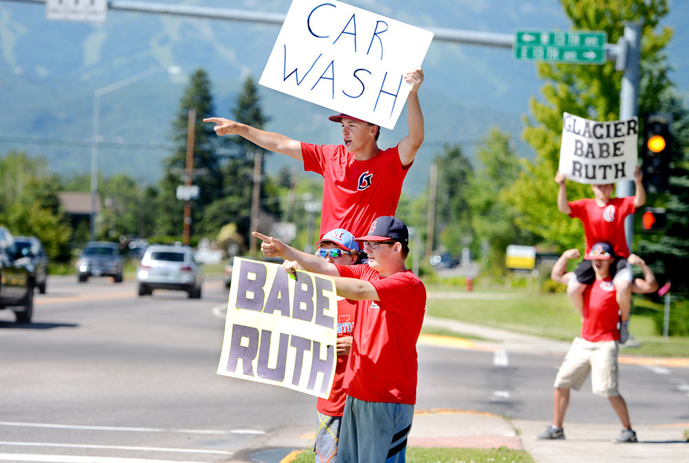 Austyn Andrachick, front to back, Hunter Palmer, and Trenton Tyree (on Palmer's shoulders) and other team members wave to cars to invite them to their fundraiser car wash on Tuesday afternoon, June 28, in Whitefish. Ironically the day the community woke up to learn the bleachers at the Sapa-Johnsrud Babe Ruth Fields has been destroyed in a fire the team members were already scheduled to do the fundraiser at the Cenex Zip Trip to help with travel expenses for tournaments.   Babe Ruth President Ray Queen said the field doesn't have any structural insurance. That means the costs of repairs will have to be met by the league. Fundraisers are still in the discussion phase but there is a GoFundMe page through which the league is trying to raise $30,000. The fire appears to have been started by someone setting off fireworks.