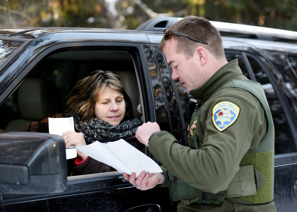 "Montana Highway Patrol Trooper Eric Thoreson goes over information and instructions with Connie Biby following his initial investigation at a fender bender near the Blasdell Volunteer Fire Department on Wednesday, January 4. Captain Duane Bowers, District 6 Commander said of their interactions with the public, ""The public support that we do have from 'silent majority' is so much larger than the resistance we face."""