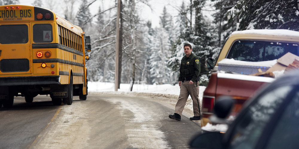 Trooper Brian Thorne's waves a school bus safely passed a disabled, abandoned vehicle on Foothill Road east of Creston on Tuesday, January 17, as he waits for a tow truck to arrive. The disabled truck unfortunately slid off the road near a turn creating dangerous hazard for vehicles wanting to go around it.