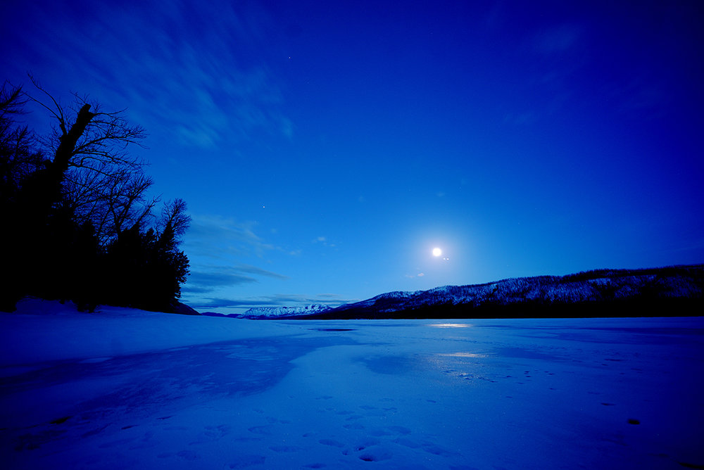 A nearly full moon setting over Lake McDonald in Glacier National Park on Sunday, February 12.