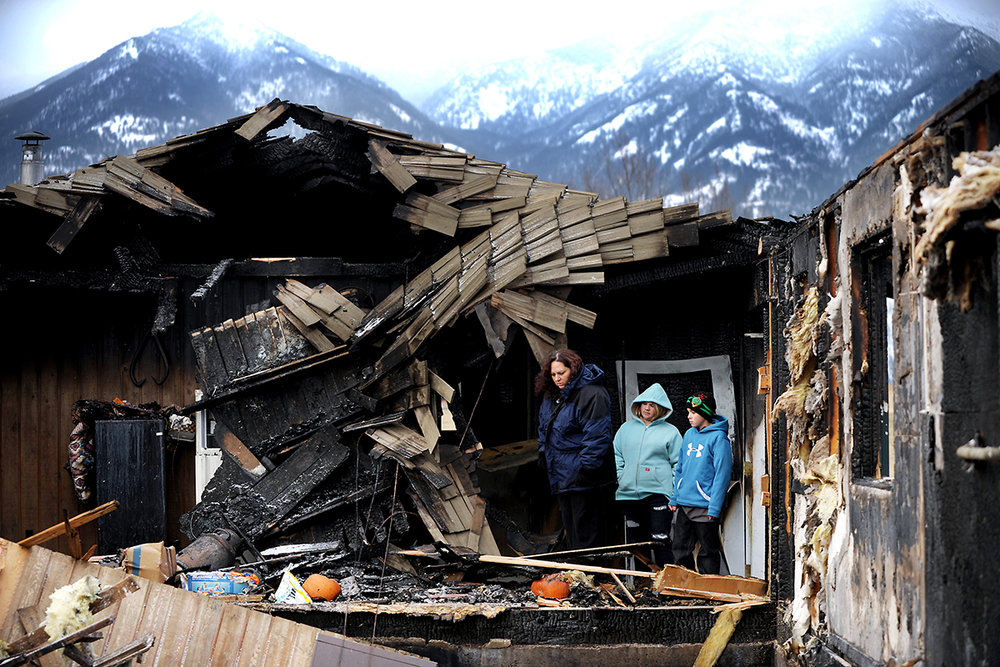 From left, single mother Hayley Matthews and her two children Darien, 12, and Kaden, 10 survey the damage to their home on Friday afternoon, Nov. 18, east of Kalispell. The Matthews home was completely destroyed in a fire on Wednesday. The fire was so intense that firefighters used 16,000 gallons of firefighting foam to combat the blaze. (11/18/11)