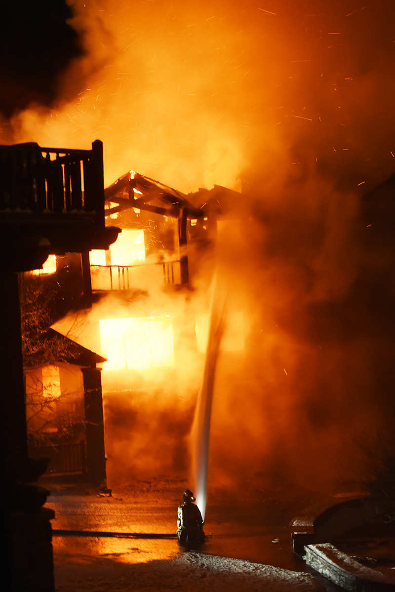 A firefighter battles the fully engulfed townhouse on Slopeside Drive on Big Mountain on Thursday night, Nov. 2, in Whitefish. At 9:42 p.m., Big Mountain Fire and Rescue responded to the report of a structure fire in a residential area near the ski slopes at Whitefish Mountain Resort. They were quickly joined by crews from the Whitefish, Kalispell, Columbia Falls and Evergreen fire departments. Nearly 30 firefighters battled the blaze for about five hours in freezing conditions on snow-packed ground. A sharp wind was another concern for firefighters as they fought to keep the blaze contained. (11/2/17)