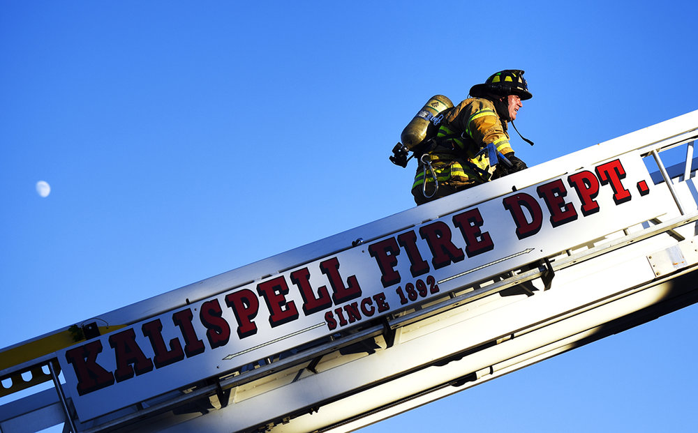 Kalispell Firefighter Jake Felts carries a tool up the ladder to firefighters dealing with the last of a fire on the roof of the old hospital building on Tuesday evening, July 4, in Kalispell. The roof fire was reported at 7:43 p.m. and was responded to by the Kalispell, Evergreen Fire and Rescue, South Kalispell, and Smith Valley departments. Kalispell Police and the Flathead County Sheriff's Office were also on scene. The original hospital building was constructed in 1911 and was remodeled into condominiums in 2007. (7/4/17)