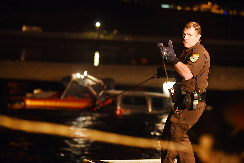 Flathead County Sheriff's deputy Dan Linder looks back at the tow truck while as he struggles to stabilize the line dive team members are working to attach to a partially submerged truck at 1:40 a.m. Monday morning, Feb. 16, in Bigfork. At 9:15 p.m. emergency crews first responded to a driver who missed the entrance to the one-lane span on Bridge Street. Law-enforcement officials have declined to identify the man because the investigation is ongoing and authorities believe alcohol was a factor. It took more than six hours to extricate the truck from the river. (2/16/15)