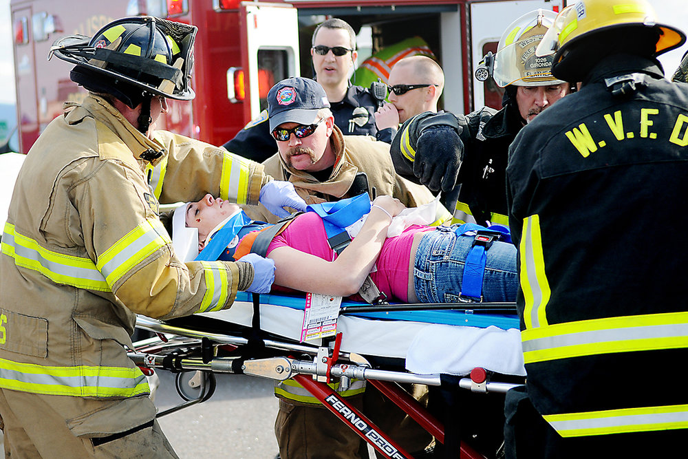 Kalispell Firefighter F. Ray Ruffato, center, carefully looks over a victim being moved into a waiting ambulance Friday evening, May 20, at the scene of a wreck at the intersection of U.S. 93 and W. Reserve Drive in Kalispell. (5/20/11)