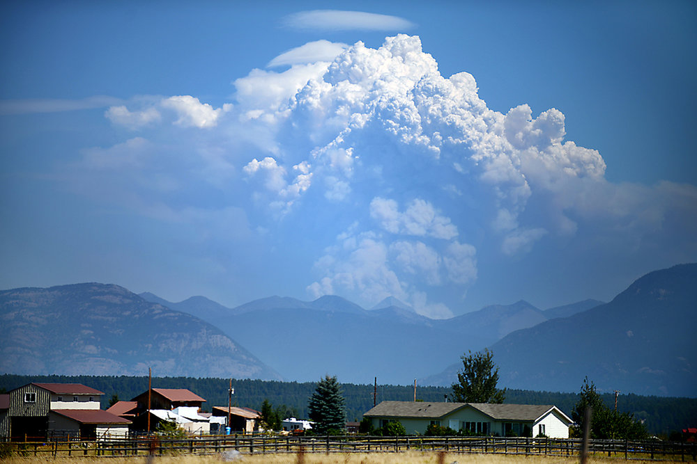Smoke from the Thompson Fire in Glacier National Park pours into the sky in this view from Lost Creek Road and Farm-to-Market Road in West Valley on Tuesday afternoon, Aug. 11. More than 30 fires are burning between the Flathead National Forest and Glacier National Park. Approximately 13,600 acres are not contained. (8/11/15)