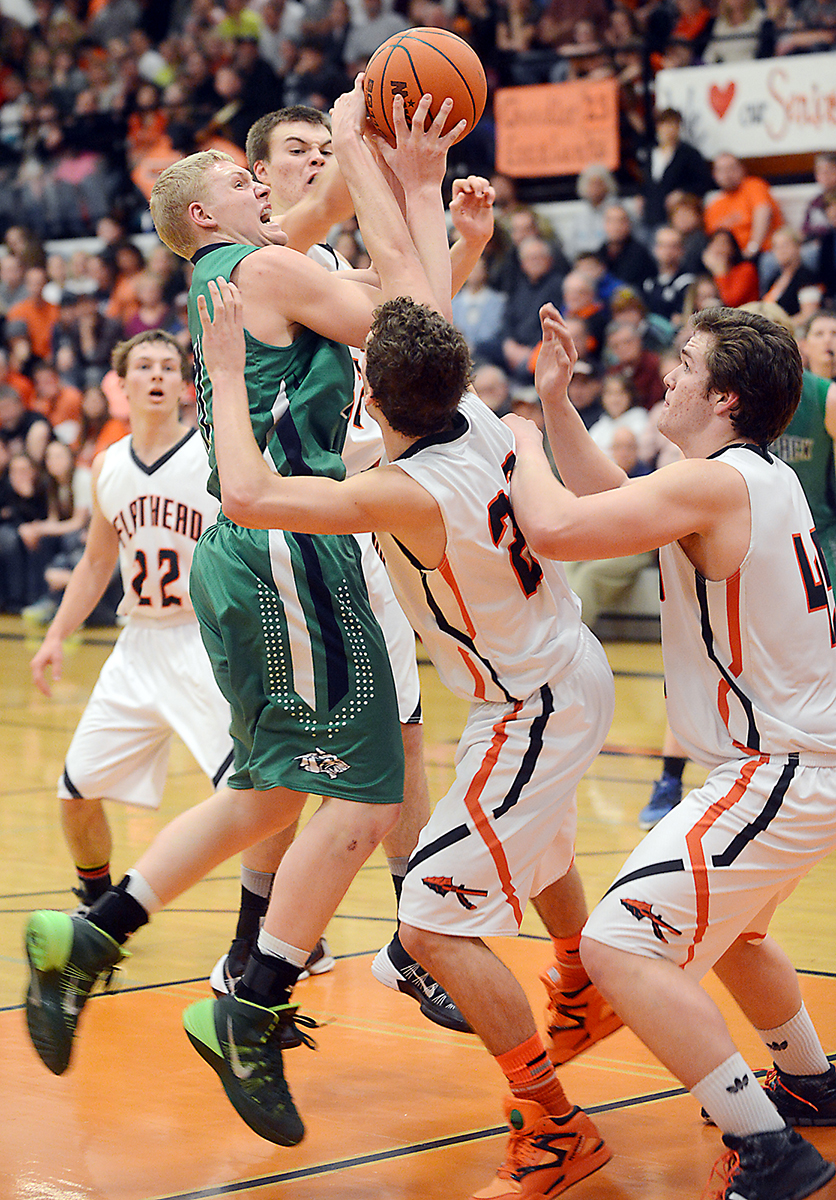 Glacier senior Bryan Michaels shoots for two under pressure from Flathead senior Matt Quist during the Crosstown match up on Friday, Feb. 28, in Kalispell. Glacier won the game 62-47. (2/28/14)