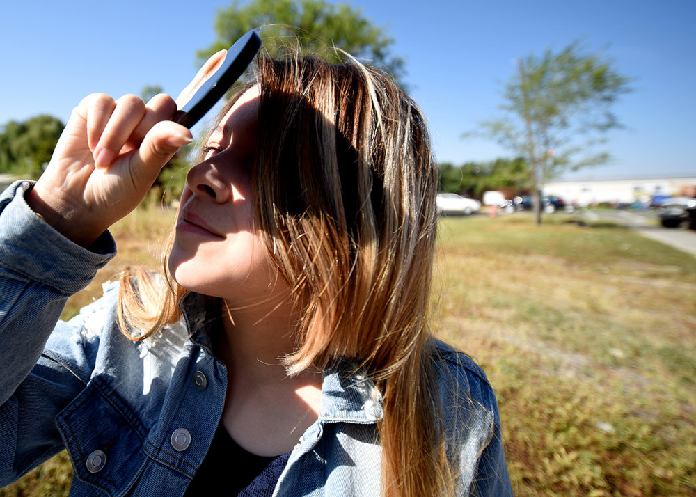 Melody Benchley, 13, of Hooper, Utah looks up at the eclipse through a disk of obsidian. Here family got the disks while traveling in South America. They were told that the obsidian is what the ancient Aztecs used to view eclipses.