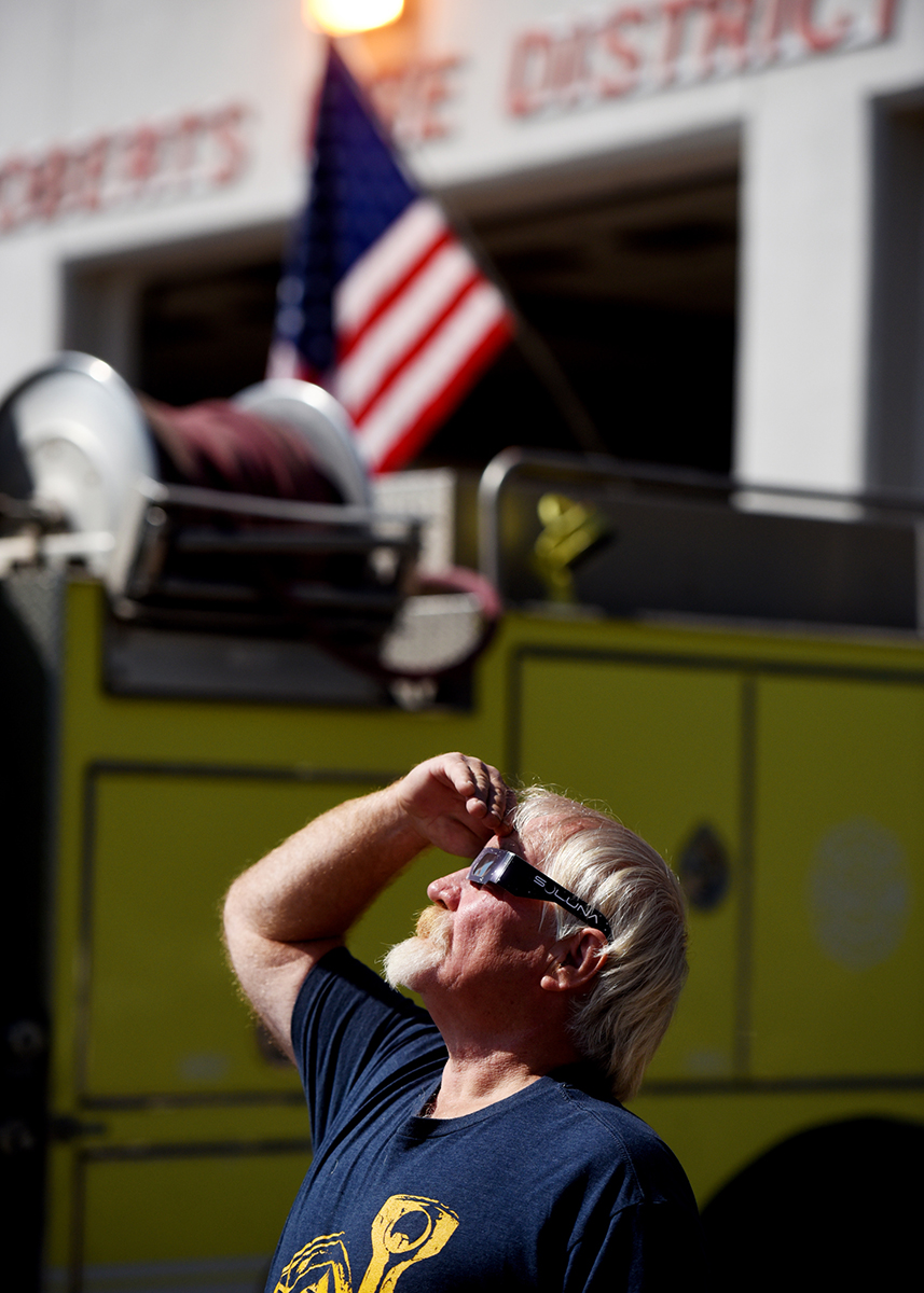 "Al Tays of Whitefish stands near the Roberts Fire District as he watches the moon begin to pass in front of the sun on August 21. Seeing totality was a ""bucket list"" item for Tays."