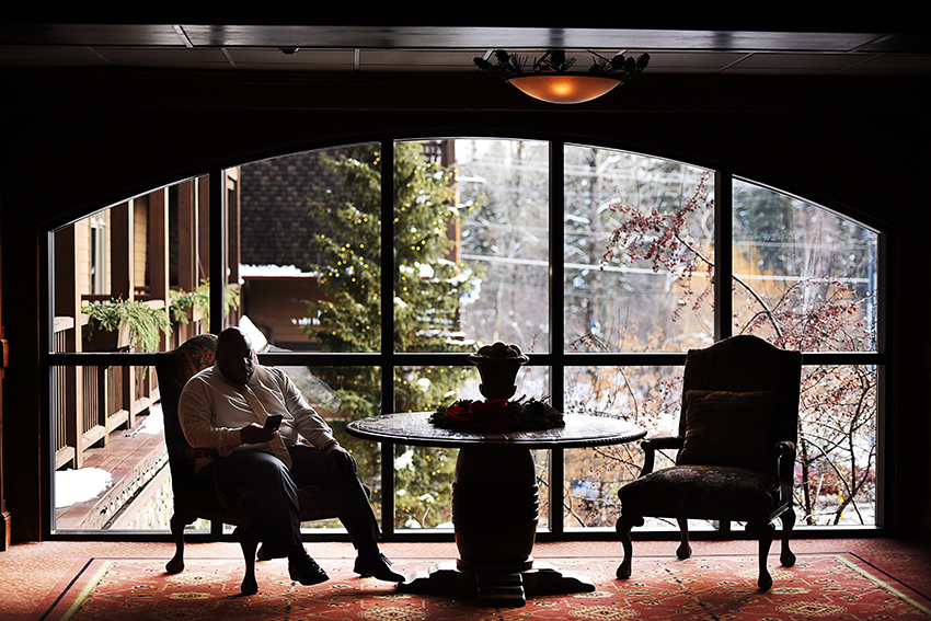 The groom waiting and answering happy birthday texts at Whitefish Lake Lodge.
