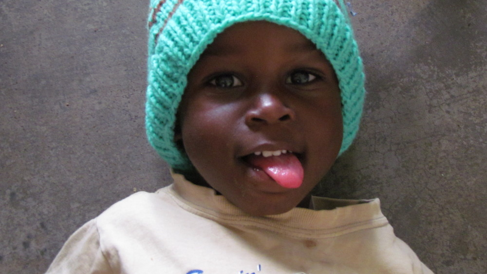 Child in a Ugandan School receiving a hat made in hand made in Canada by volunteers - he shows his appreciation!