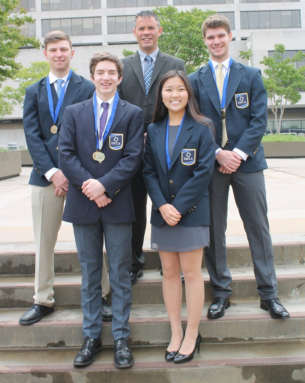 Adviser, Chris Gapinski, pictured with the four LHS DECA finalists.