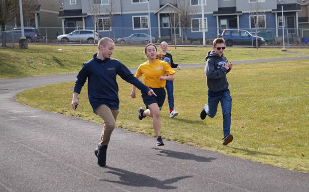 Cadets Chandler Alexander, Kerrek Matson, and Olivia Van Ry push Cadet Taylor-Nicole Le (10) to finish strong during the mile run.