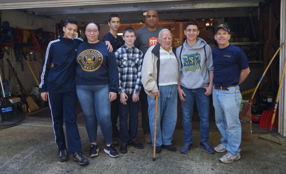 Chief Spears, Captain Deehr, and Cadets (from left to right) Fox Mercury, Aurora Baldwin, Evan Rosenfelt, Joshua Pullins, Danial Morrelli, and Giovanni Francavilla (not pictured) gathered at the home of Mr. Dale Brown, a 95 year old World War II veteran who needed some assistance cleaning up his yard after the harsh winter.