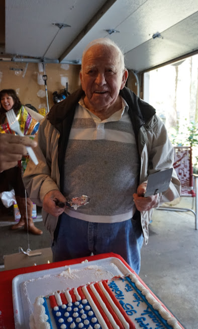 Mr. Dale Brown, who was stationed in Europe during WWII, cuts and serves his 95th birthday cake after Cadets and other volunteers finished clearing his yard of winter debris.