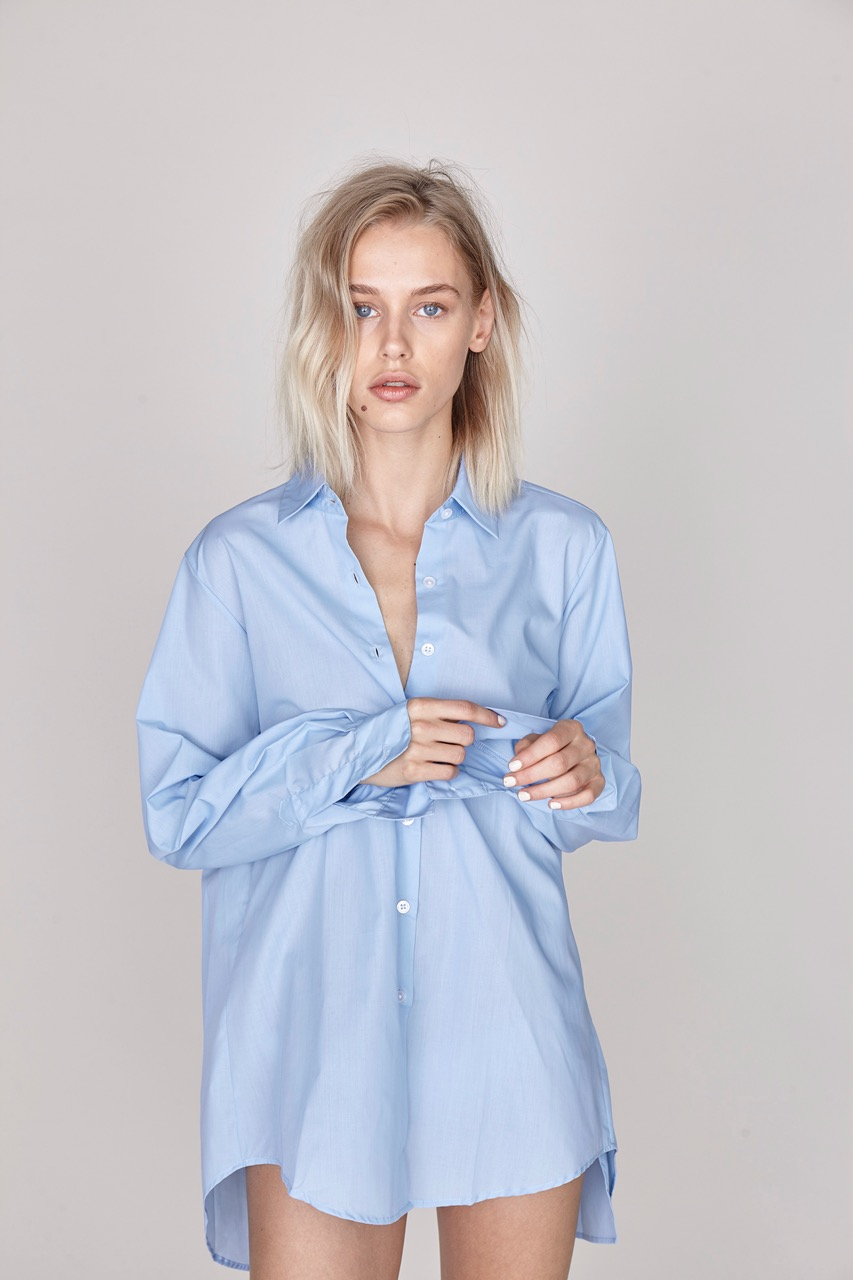 ELIN OXFORD SHIRT - A light blue Oxford shirt crafted from crisp cotton poplin and cut in a loose fit. The deep slit in the back and contrasting shell buttons make for a relaxed feminine take on classic shirting – for warm and romantic summer days on the run. 60% cotton. 40% polyester. Made in Portugal.