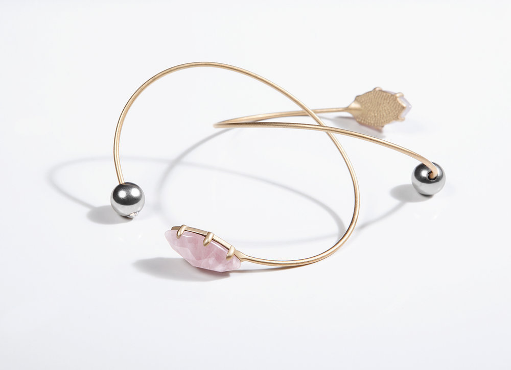 NOVA BRACELET - This lightweight, delicate and bendable cuff, represents the storyline of two celestial bodies that differ from on another just to complement each other. Balancing a rose quartz element on one side, and a micro sphere carrying an encrusted gray opal, this clean and modern piece exudes a sense of effortlessness. 18k antiqued gold-plated, antiqued silver-plated, rose quartz, swarovski crystals adjustable. Natural gemstone's inclusions may differ from piece to piece to allow for a signature one-of-a-kind aesthetic. Made with love.