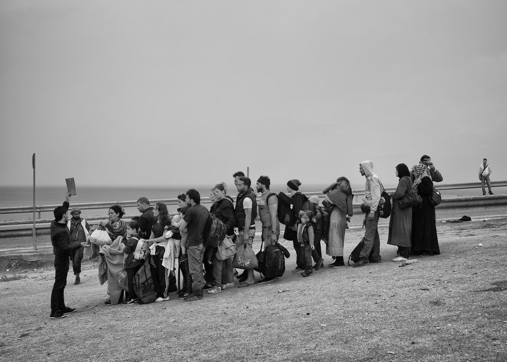 Refugees wait in a queue for a bus organized by the local NGOs to go toward registration camp near Mytilene on September 23, 2015.