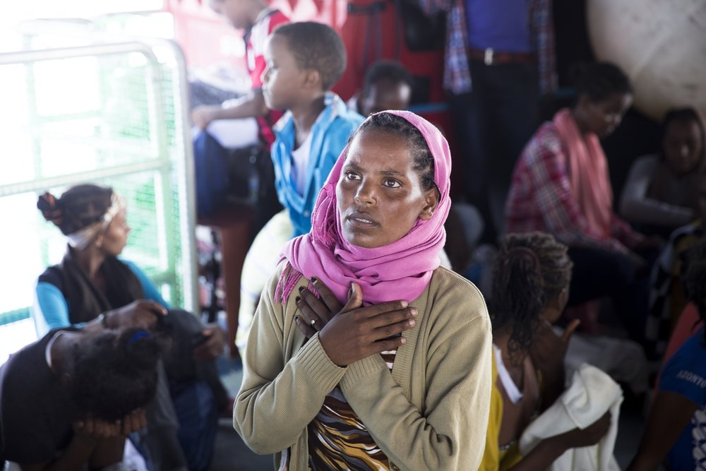 Strait of Sicily, September 2, 2015, a woman praying after been rescued. 40 miles from the Libyan coast , MOAS/MSF Holland team are rescuing two old wooden boat coming from Libya with 550 people on board. All the refugees in these boats where coming from Eritrea and they have been embarked in the Libyan port of Zuwarah.