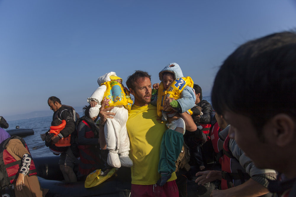 A Spanish volunteer lifeguard helps refugees arrive on the Greek island of Lesbos.