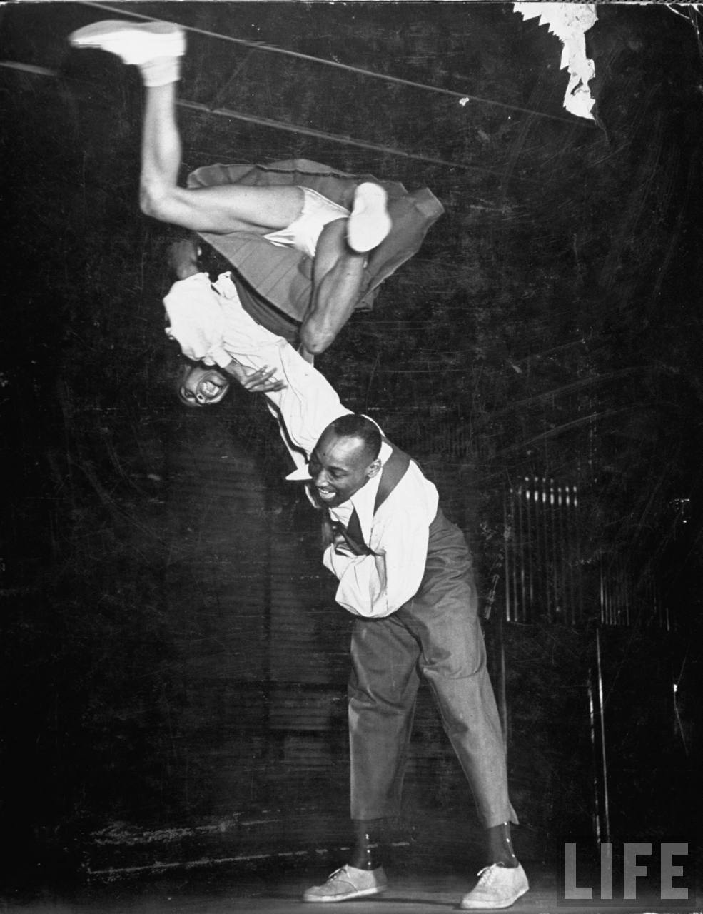 Frankie Manning swinging his partner around the back.