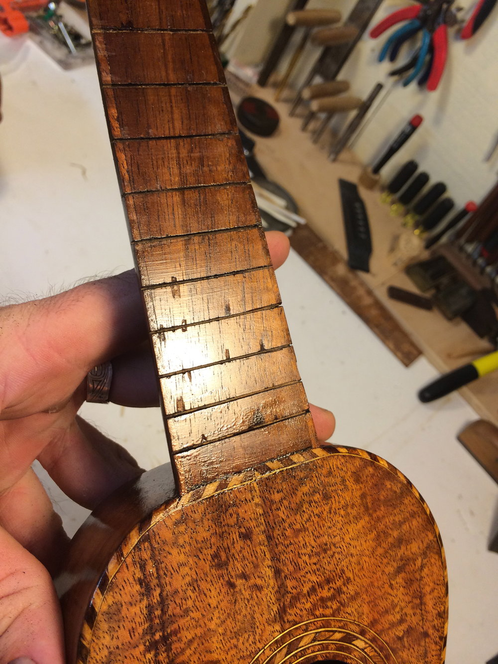 These early ukes often had light finish over the fingerboard, These little chipouts are going to disappear.