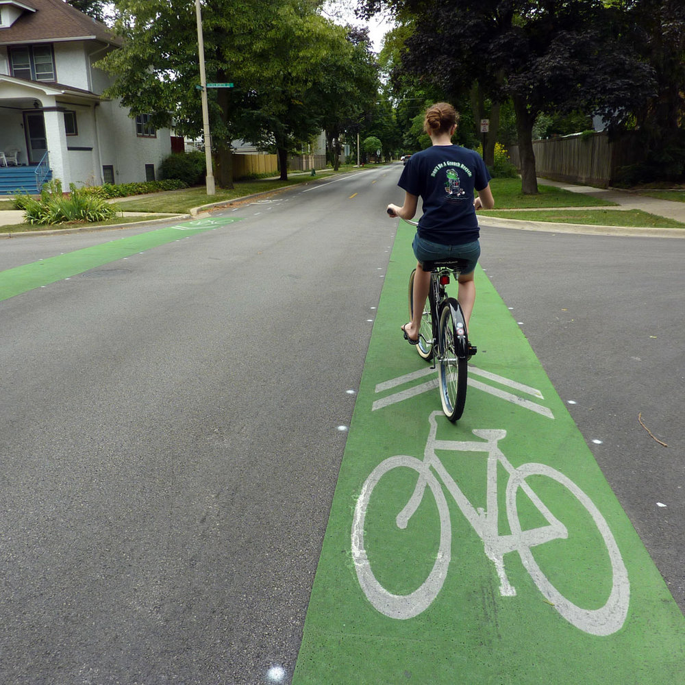 Girl riding a bike in the bike lane.