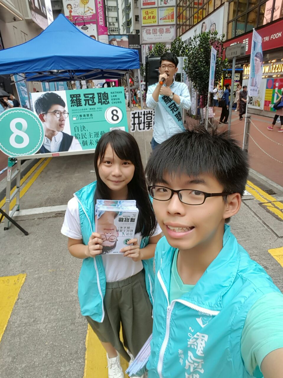 Agnes Chow Ting (left) and Joshua Wong (right) on the street campaigning for Demosisto's Chairman, Nathan Law (back). (Photo: Facebook/Joshua Wong)