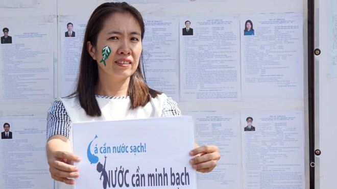 "Blogger Mẹ Nấm holds a sign reading ""Fish need clean water, the people need transparency."" (Photo: Facebook/Nguyễn Ngọc Như Qùỳnh)"