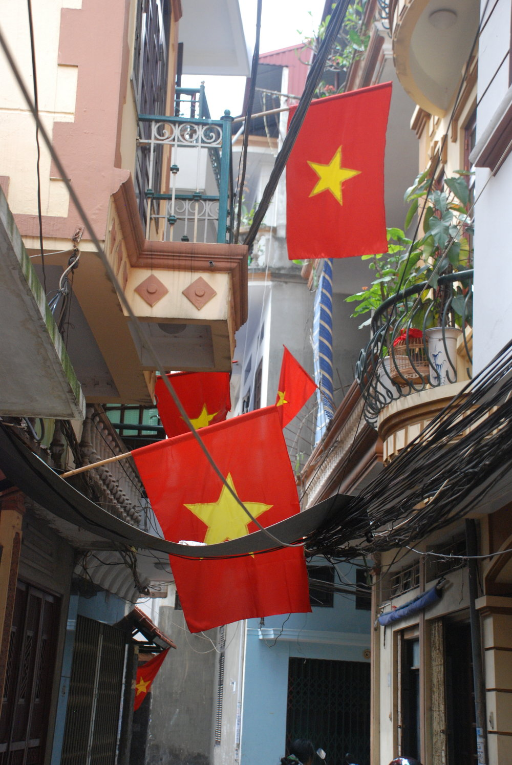 An alleyway in Hà Nội is decorated in flags. (Photo:  Aaron Brown )