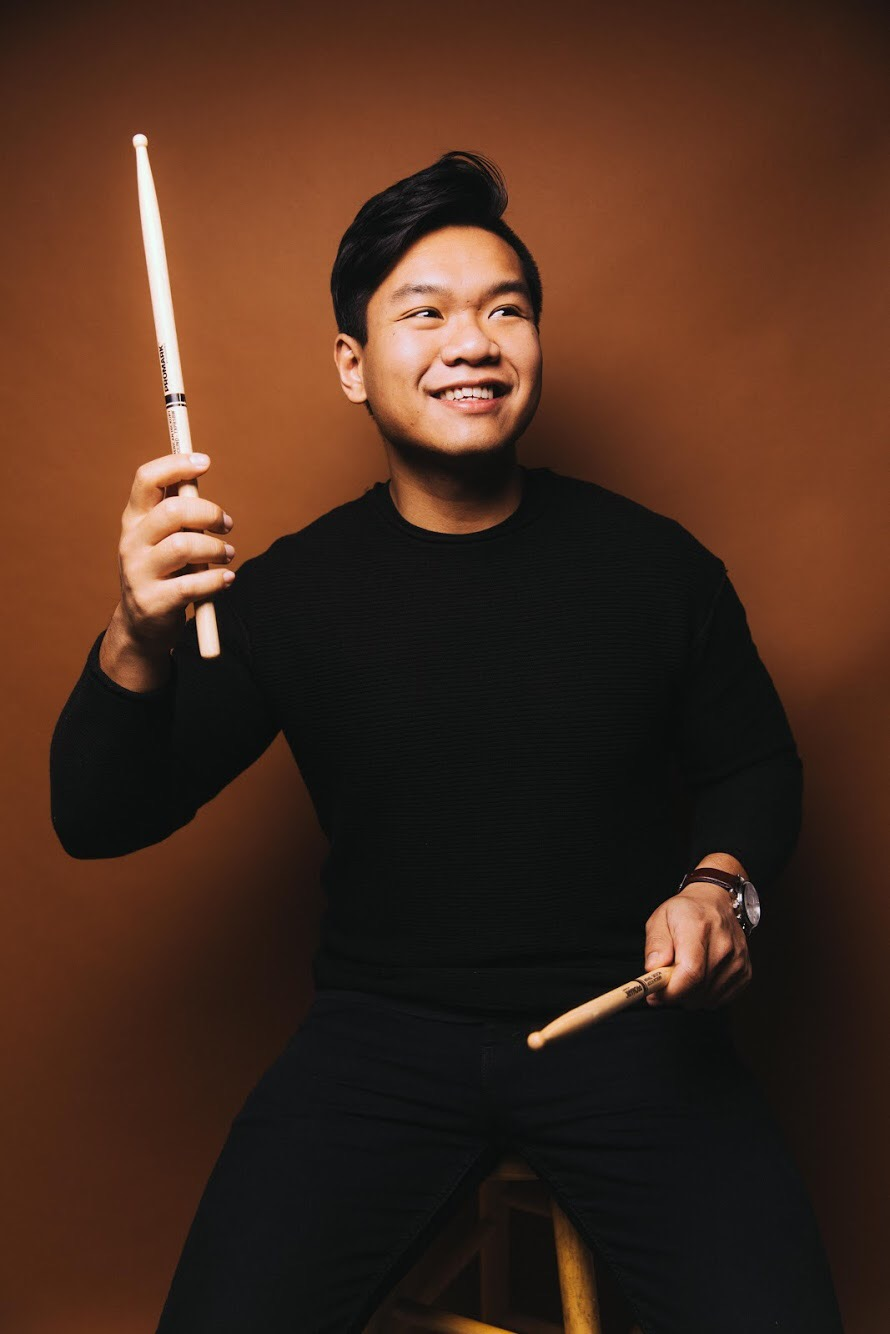 Jon Singngam,  Percussion    Jon Singngam, Drums, hails from Meriden CT and holds a BA in Political Science with a minor in Sociology. When he isn't playing the drums he is an Aviation Account Manager for Aerotek in the Northeast. Jon began playing drums at age 7 and currently plays on Ludwig drums, Meinl cymbals and Vater Sticks. Jon first trained in classical percussion techniques through concert, symphonic, and marching band throughout primary school and college at UConn. Jon's major musical influences include Tony Royster Jr, Benny Greb, Kyoshi Ijichi, Jason McGerr, and Travis Barker. At any time he can be contacted for lessons or performance opportunities at jon.singngam@gmail.com.