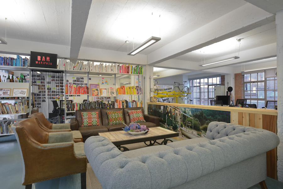 A bright, colorful and cozy breakout area in ideo's london office, filled with sofas, art, decor and a long bookshelf