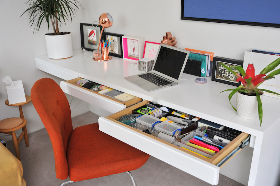 A red chair sits against a clean, bright white home office, where the modular desk has multiple drawers pulled out to show the detailed and efficient organisation inside.